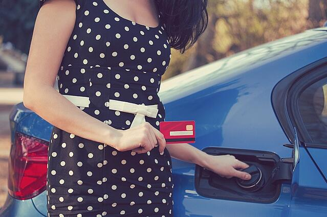 Freelance business woman filling car with gas.jpg