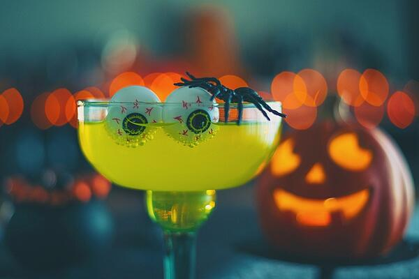yellow festive Halloween drink with eyeballs and spider for decoration