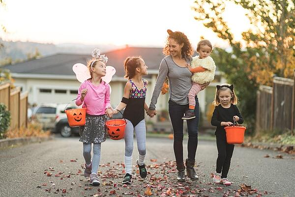 adult trick or treating with group of young children before dusk