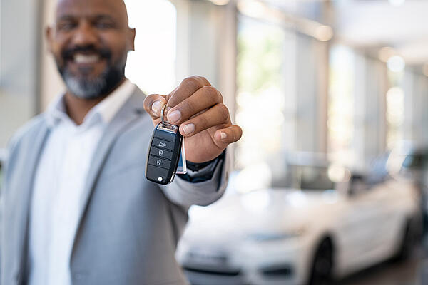 african american man holding keys in florida car dealership