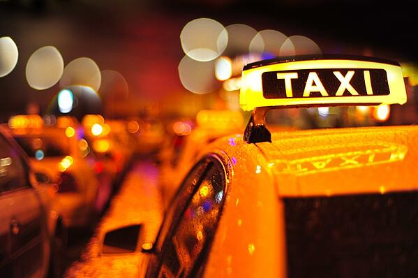 yellow taxi lined up in city wet from rain