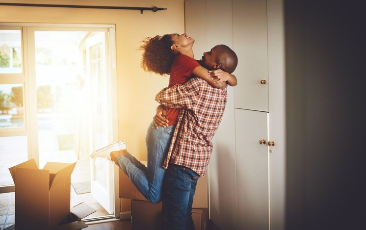 A happy couple is embracing with the holding his partner in the air with joy. They are celebrating the purchase of their new house.