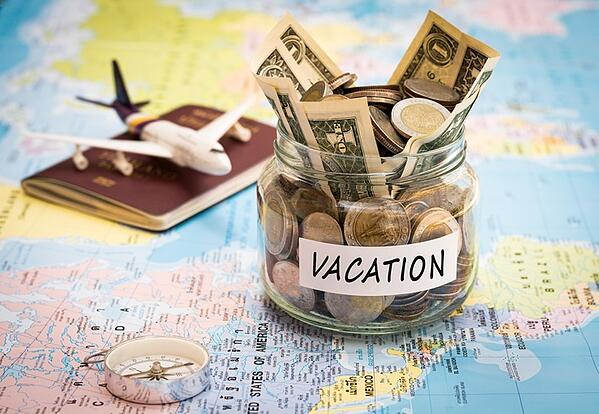 Vacation  money inside of a jar placed on top of map