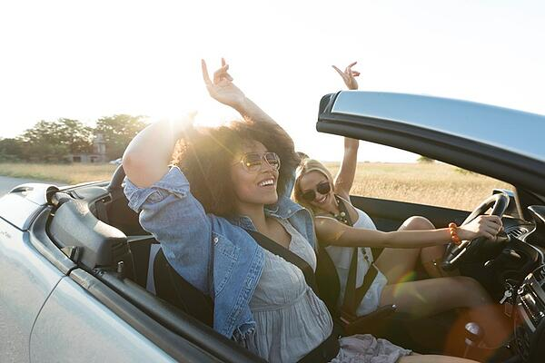 Young women singing and having fun on road trip with convertible car.