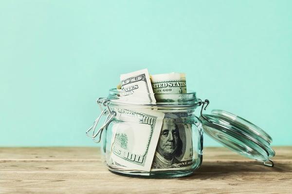 clear jar filled with hundred dollar bills