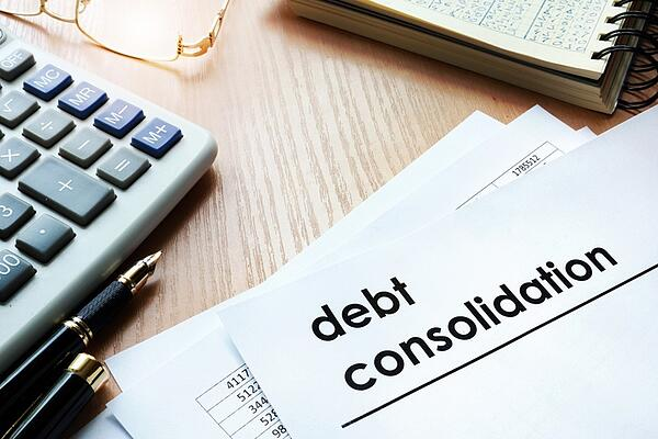 debt consolidation paper with computer and notebook
