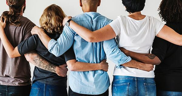 diverse group of people holding their arms around each other