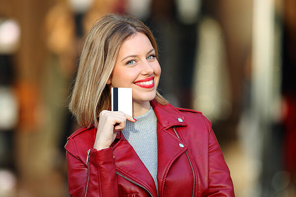 girl in red smiling with credit card in hand