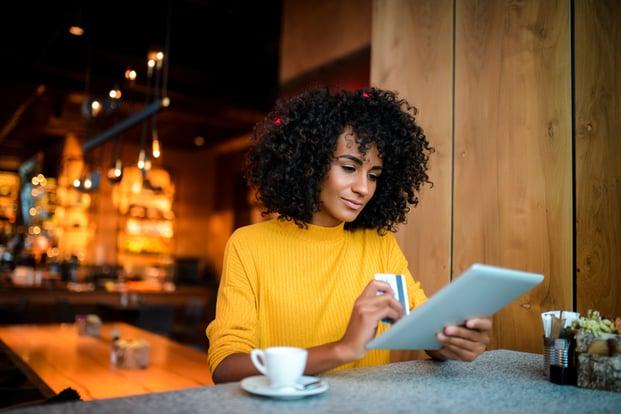 girl in yellow sweater on ipad in miami coffee shop