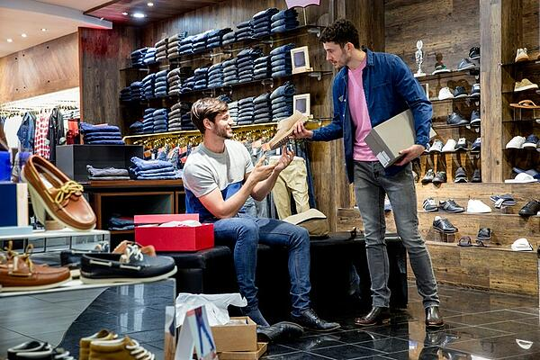 male shoe salesman helping out male customer