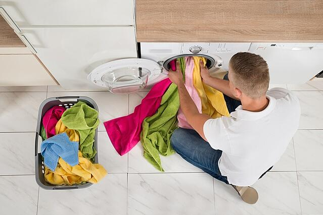 man filling washing machine with clothes