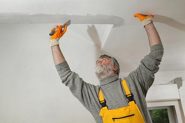 older man fixing popcorn ceiling