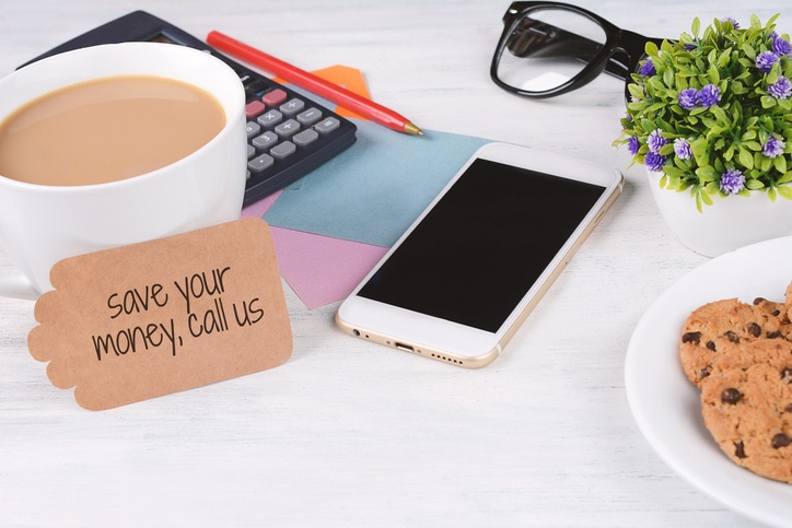 paper note with text 'save your money, call us' with coffee, cookies and calculator on white wooden background