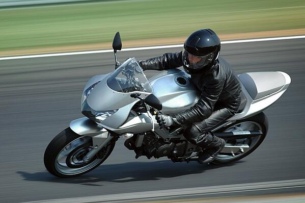 rider going fast on silver sporty motorcycle