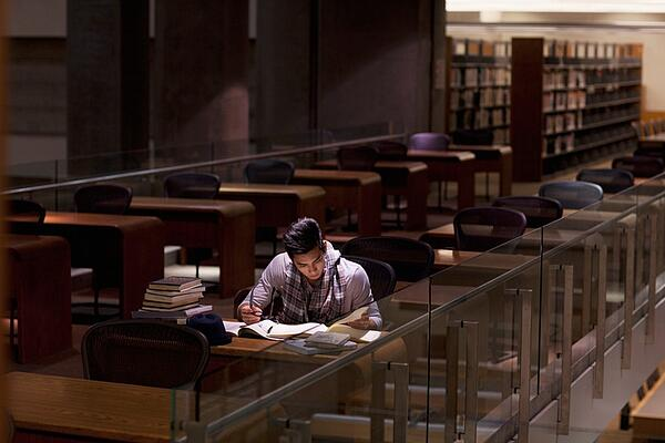 student studying in college library at night