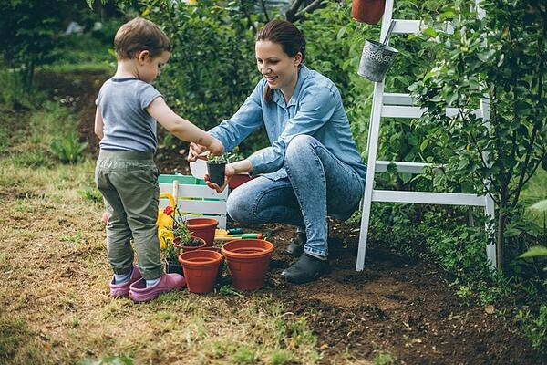 toddler and mother watering potted plants in garden
