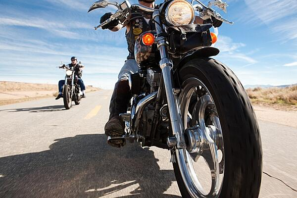 two men riding motorcycle on open road