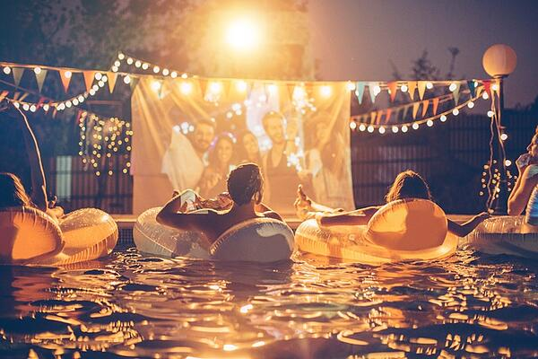 young friends light up pool party at night