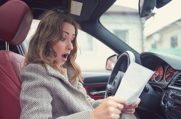 young girl reading fine print in car suprised