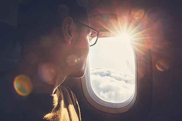 young guy looking out the window on an air plane