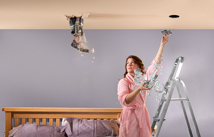 A husband's foot comes through the bad floor of his attic as his wife is hanging a chandelier in their bedroom.