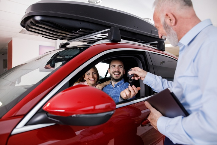 Couple receiving keys from salesman