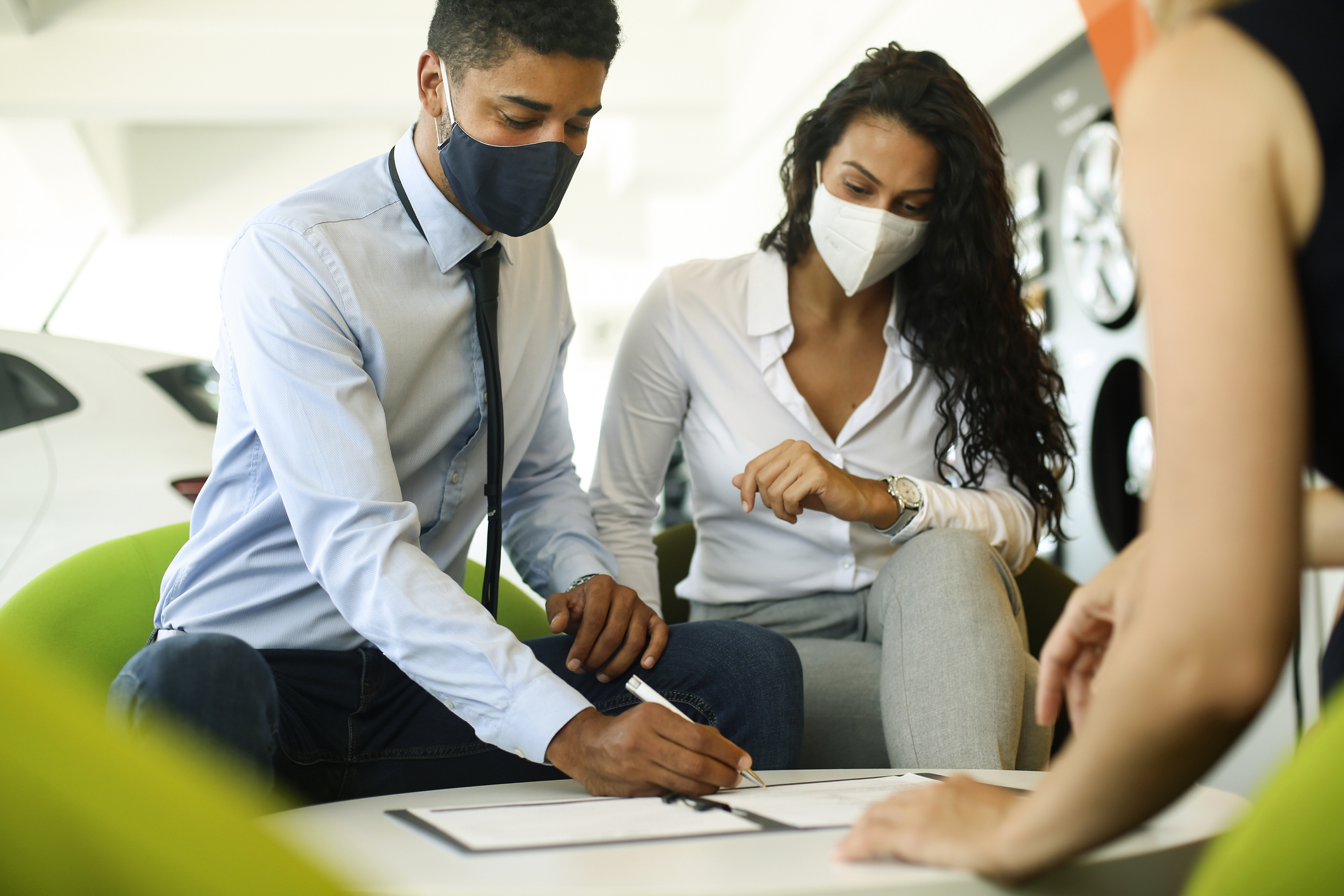 Couple wearing masks purchasing used car in florida