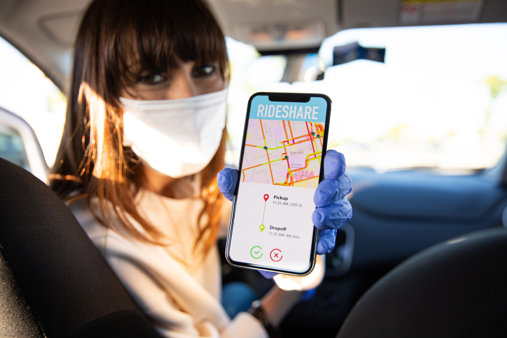 Rideshare driver holding phone with mask on