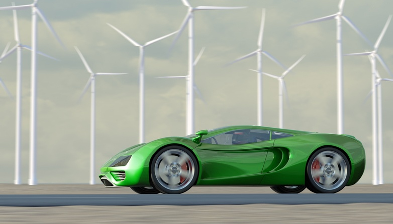 green sportscar speeding past turbines