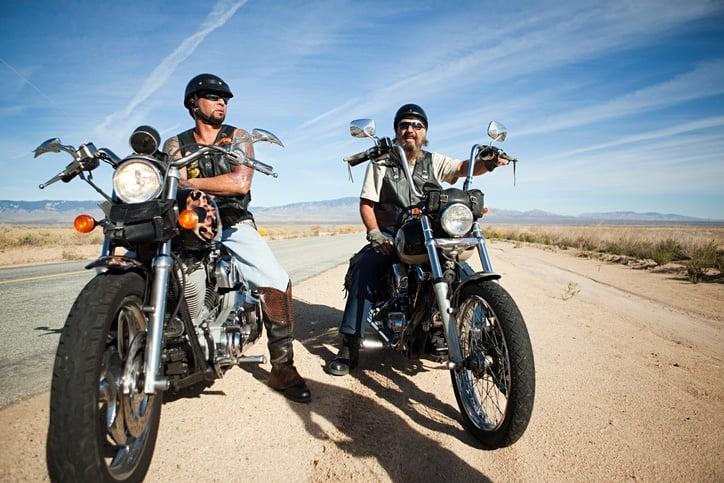 two men on motorcycles on roadside