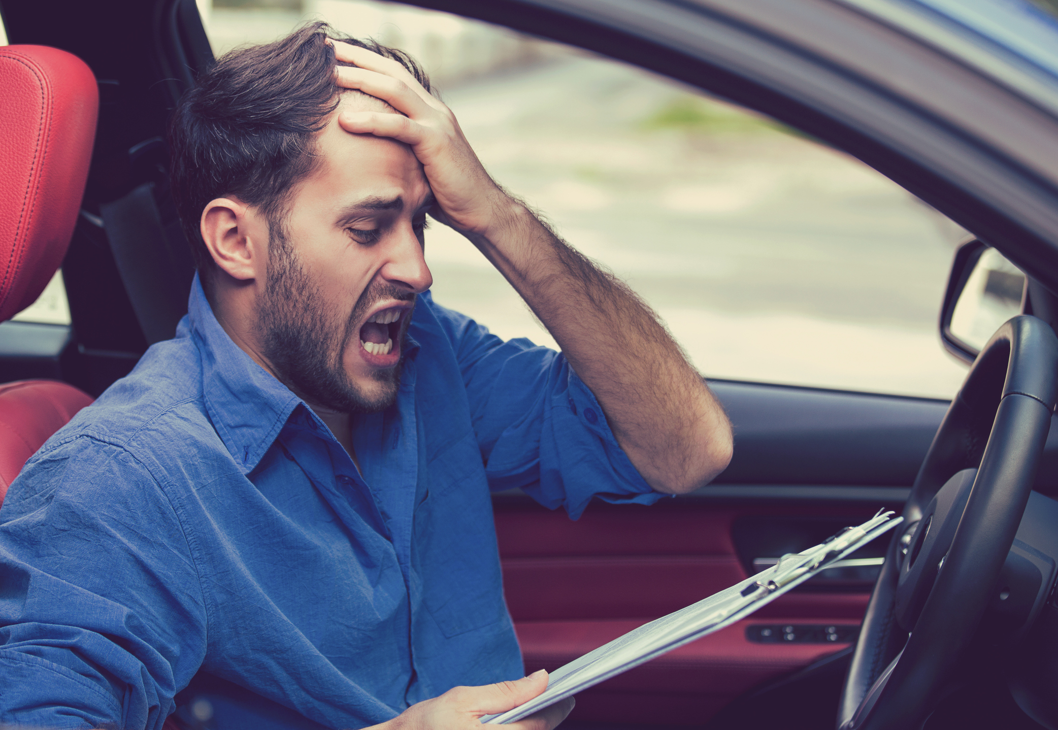 young man stressed reading fine print in car